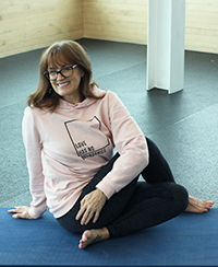 Female yoga instructor sitting with crossed legs on blue mat